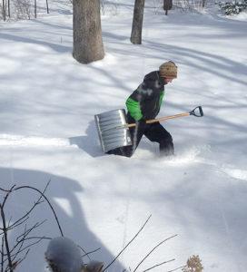 Walking through snow with shovel.